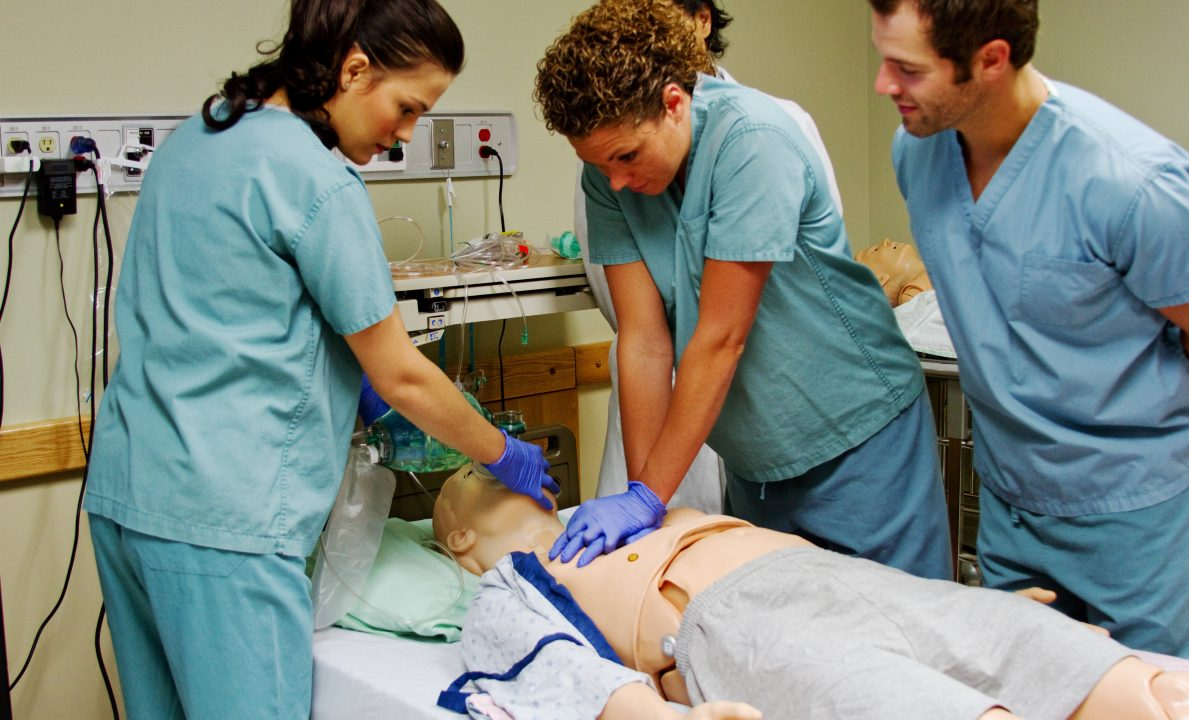 Medical staff practice CPR on mannequin